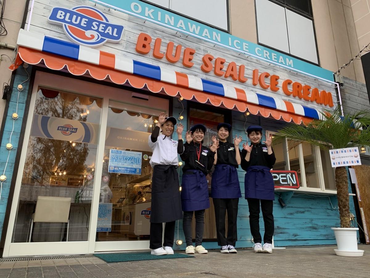 BLUE SEAL店舗の前でほほえむ店長の黒澤さんとスタッフの皆さん