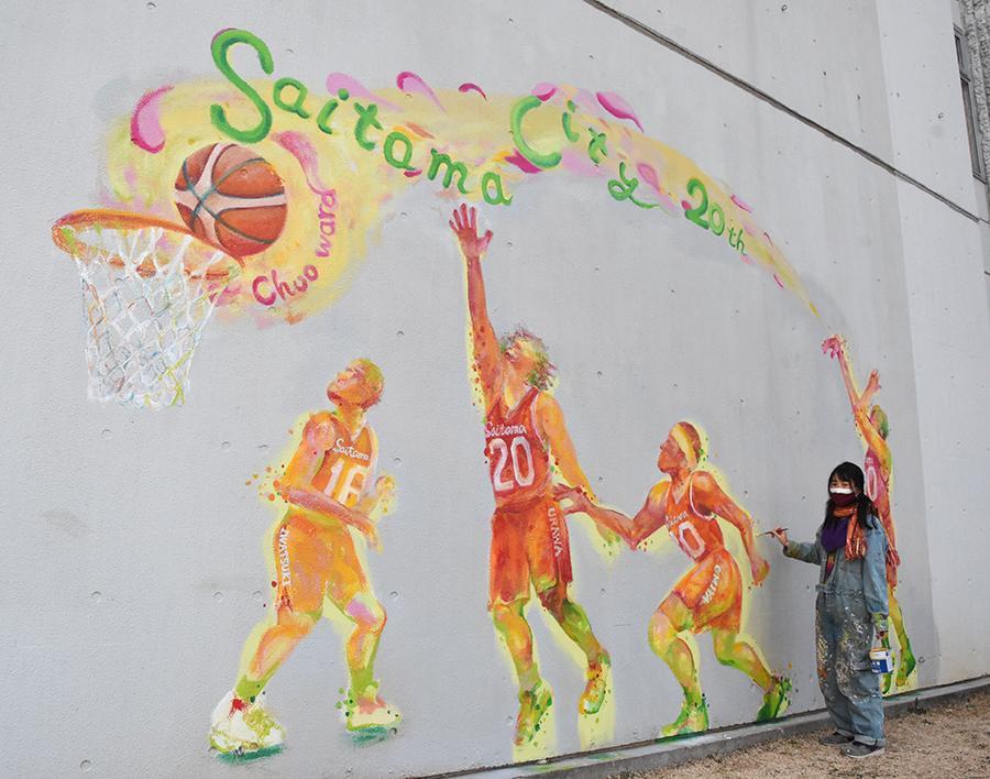 バスケットボールの試合の様子が色鮮やかに描かれたさいたま市中央区役所の外壁。奥は作業する画家、寿の色さん