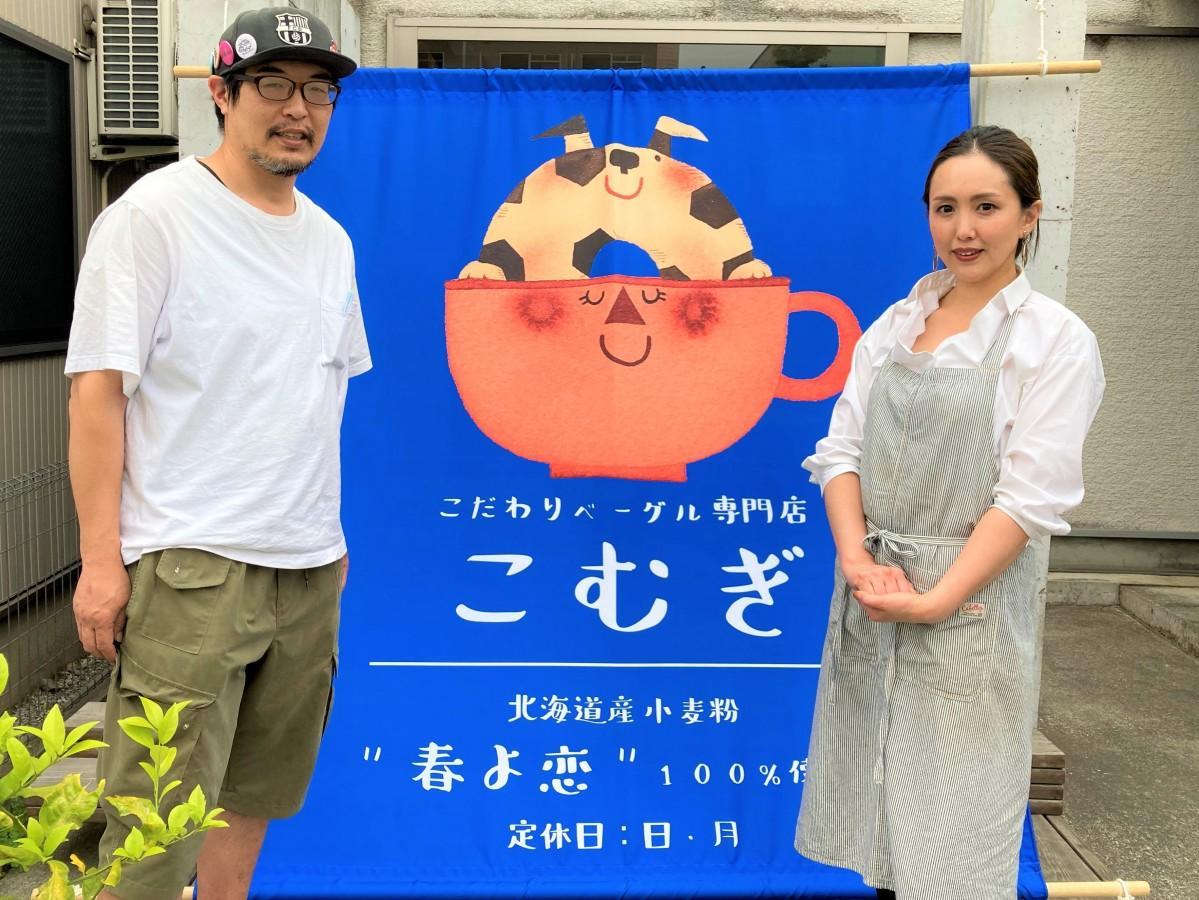 5周年記念に友人たちから寄贈された日よけ幕を前に。店長の戸草内陽介さんと知代さん