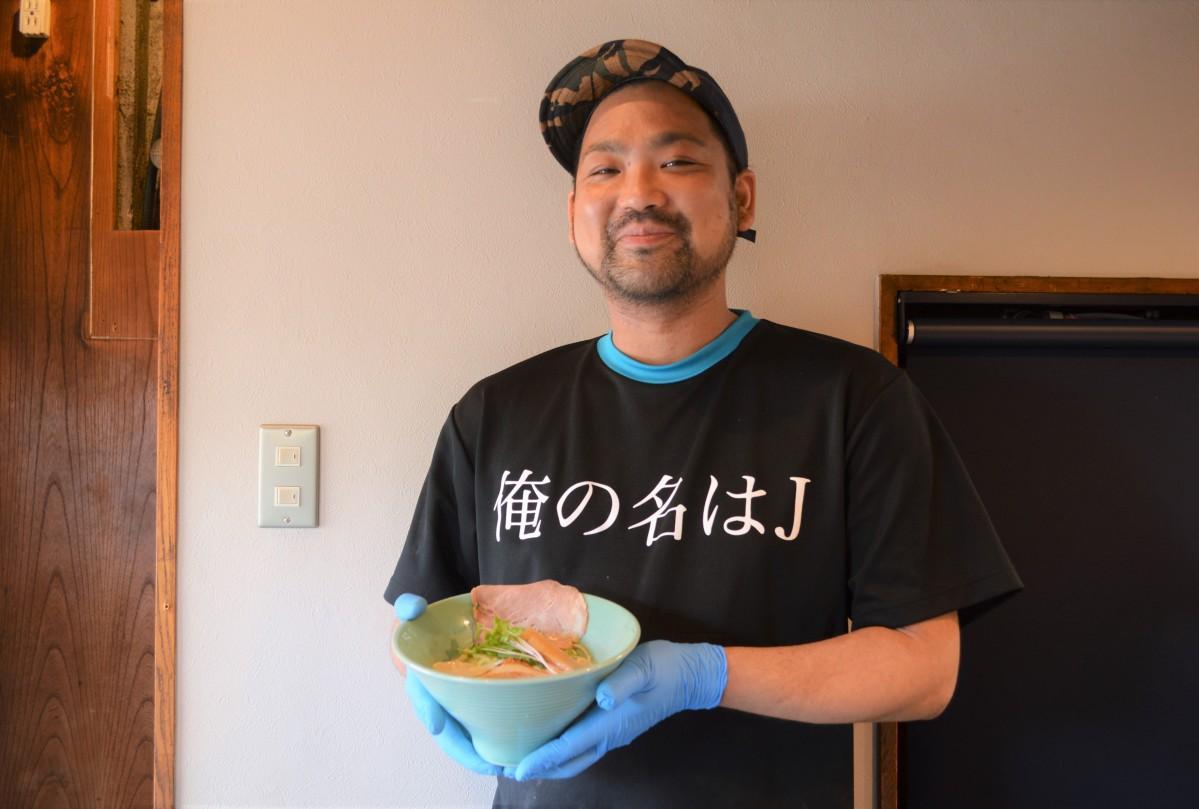 笑顔でとんこつラーメンを持つ岡淳さん