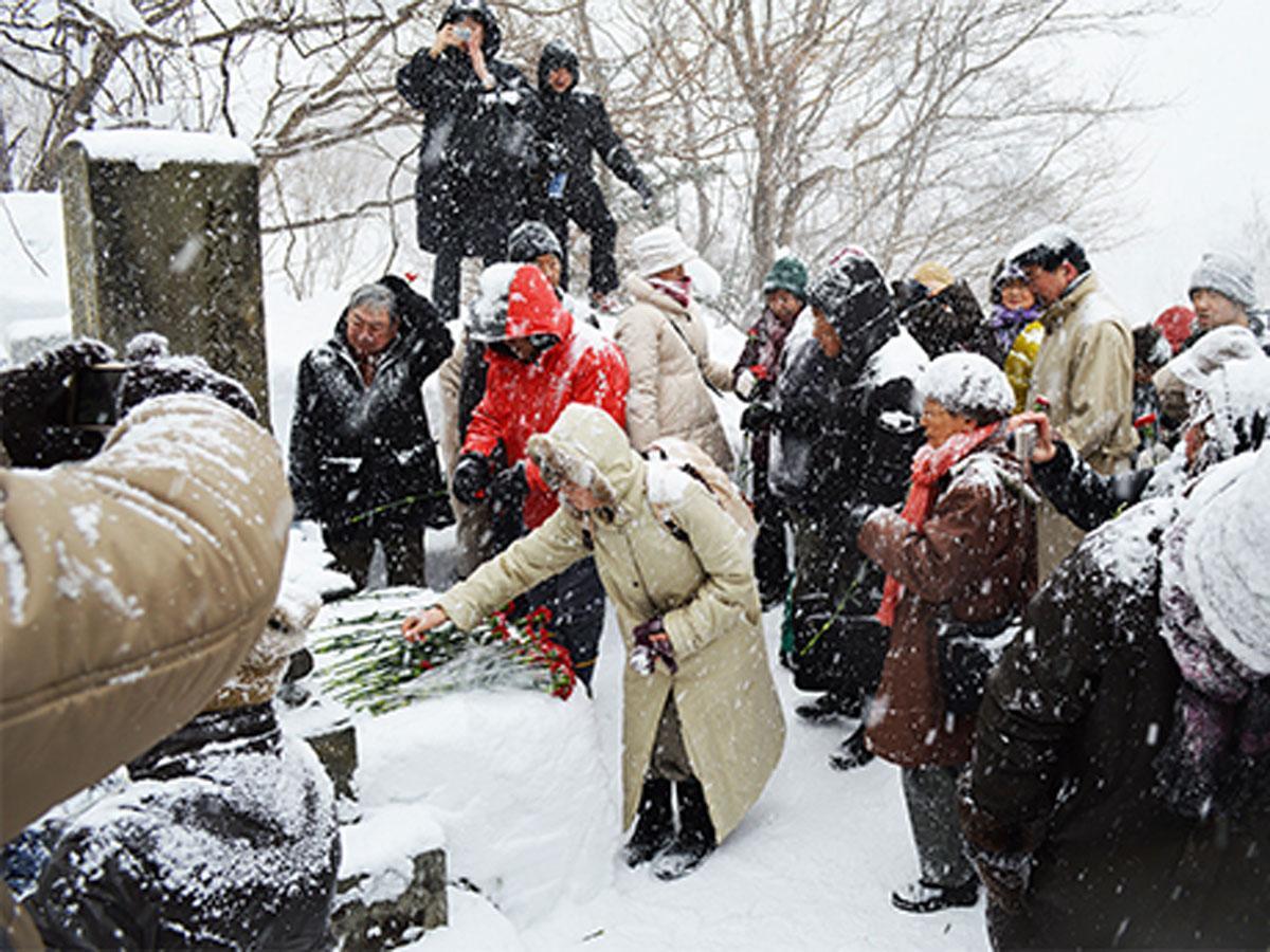 吹雪の中、長く続く献花の列