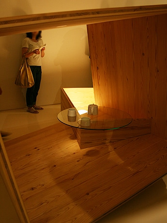 ギャラリー内に設置される、四角に組んだ木を複数組み合わせてテーブル状の機能を持たせた作品。