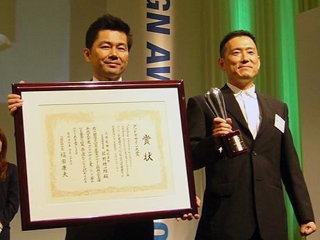 賞状を手にする三洋電機ブランド本部アドバンストデザインセンターの清水正人所長と、トロフィーを手にする小田慎二課長。