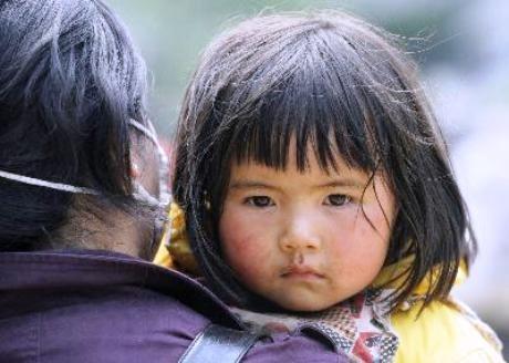 ボランティアに抱えられ、避難する女児(2008年5月16日 四川省綿陽市北川県) 写真提供=共同通信社/協力=東京写真記者協会