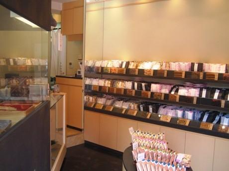 店内の左側は「かりんとまん」を揚げるスペース、右側に50種類のかりんとうがディスプレーされた棚がある。