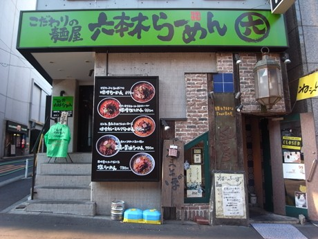 緑のベースに黒い文字の看板が目を引くエントランス