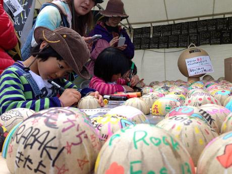 花火にメッセージを書き込む子どもたち(今年4月宮城県でのイベントの様子)