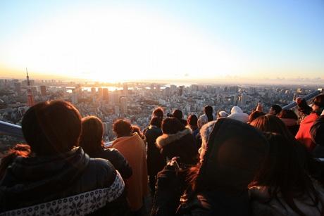 屋上「スカイデッキ」から日の出を眺める人々