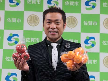 贈呈された佐賀市のトマトとミカンを手に笑顔のはなわさん