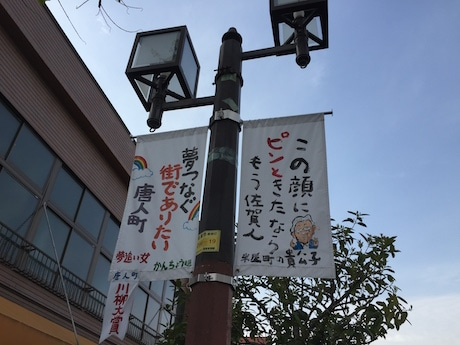 佐賀市唐人町通り沿いに商店街をテーマに川柳作品を書いたタペストリーがはためく