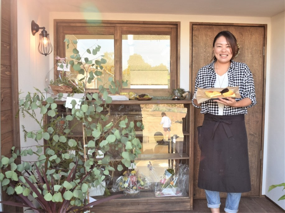 「なつの実」店舗の前で商品をPRする店主の小野奈津美さん