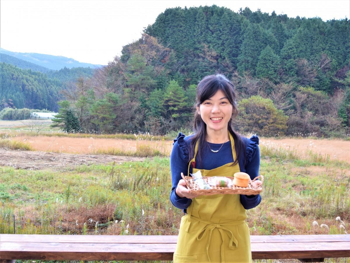 「天然菓房 のがり」のテラスで手作り菓子を手に笑顔を見せる店主の吉良朋美さん