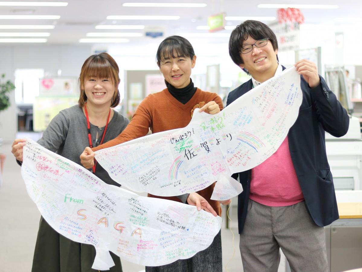 寄せ書きが集まったハト風船を掲げる富田万里さん(中央)と佐賀市市民活動プラザスタッフ