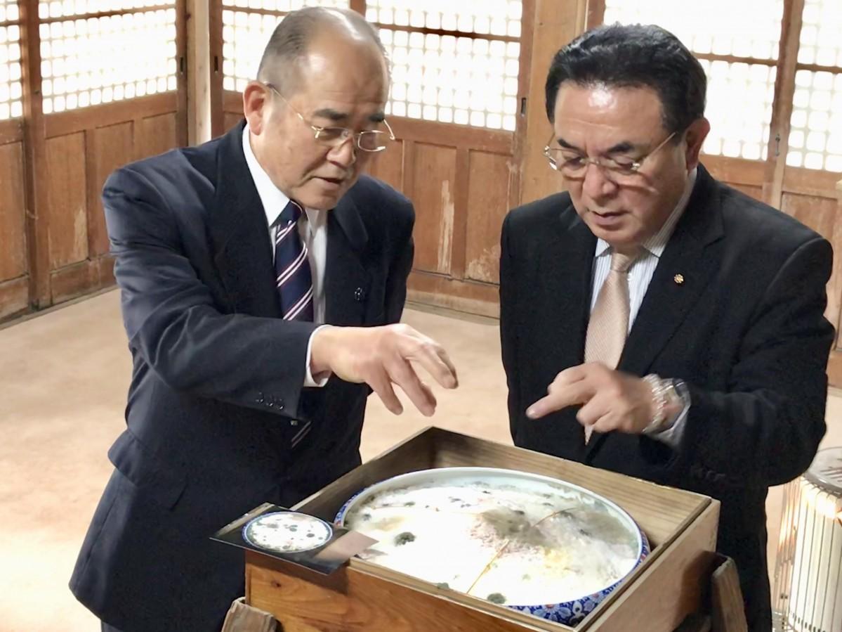 今年の「お粥占い」を説明する川崎直幸さん(右)と佐賀市の秀島敏行市長(左)