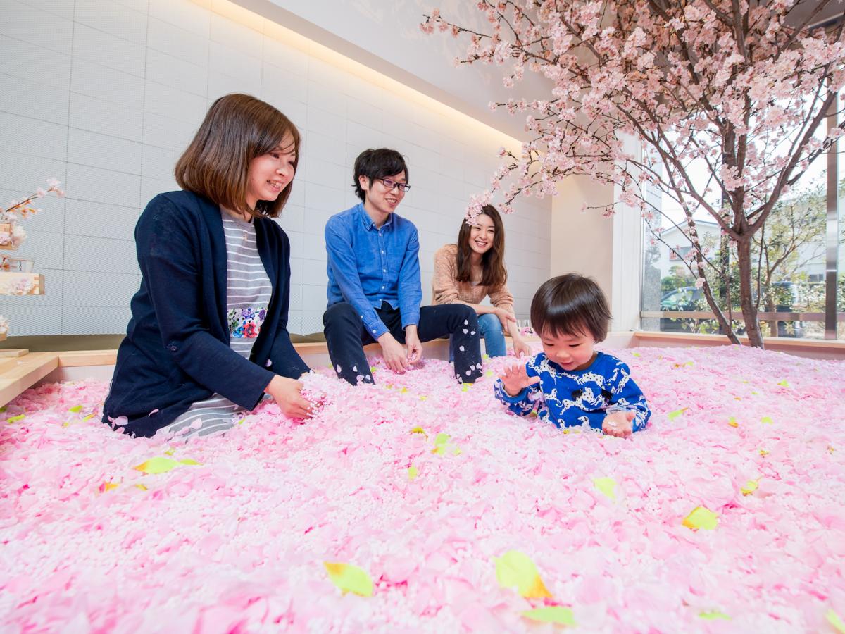 桜の花びらに埋もれる子連れの来店者