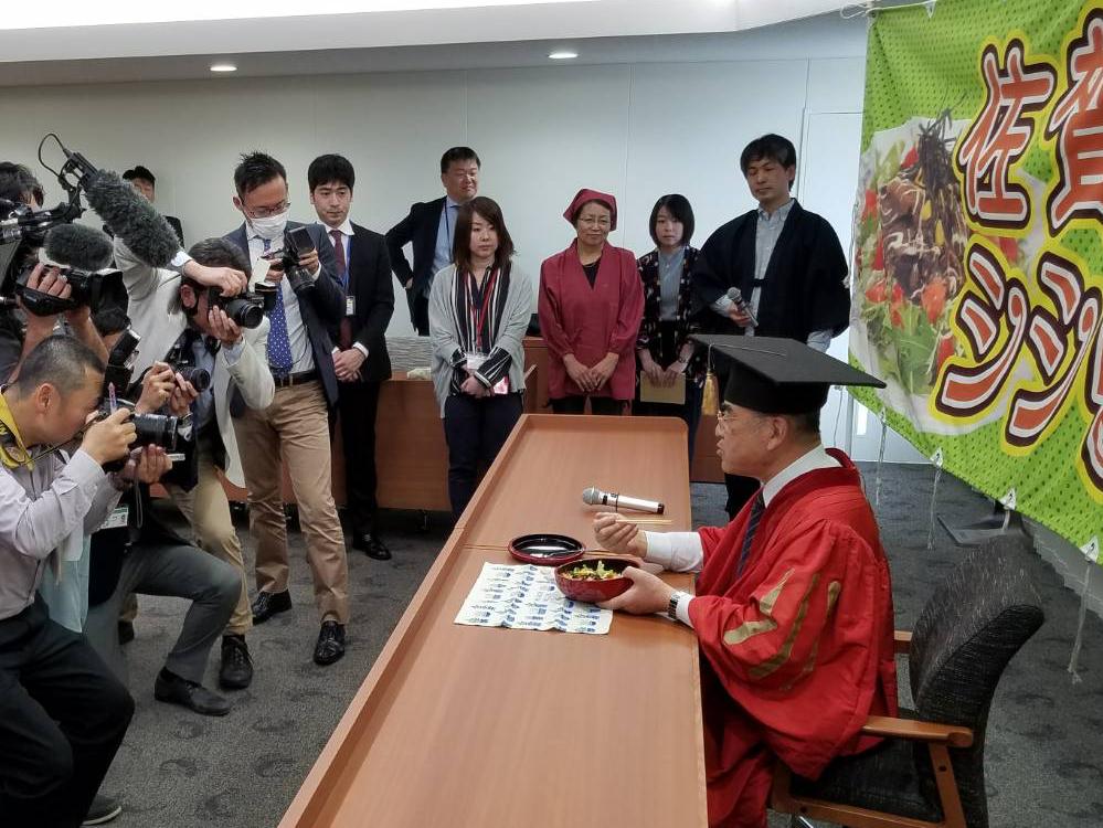取材記者らがカメラを構える中、「シシリアンライス明治維新バージョン」を試食する佐賀市の秀島敏行市長