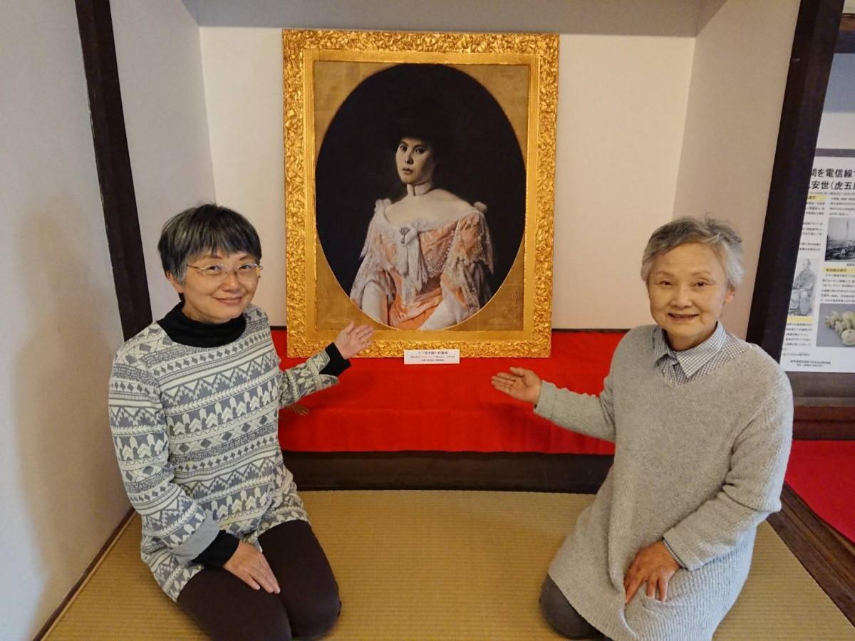 日下部米鶴の肖像画を示す末岡暁美さん(左)と南里早智子さん(右)