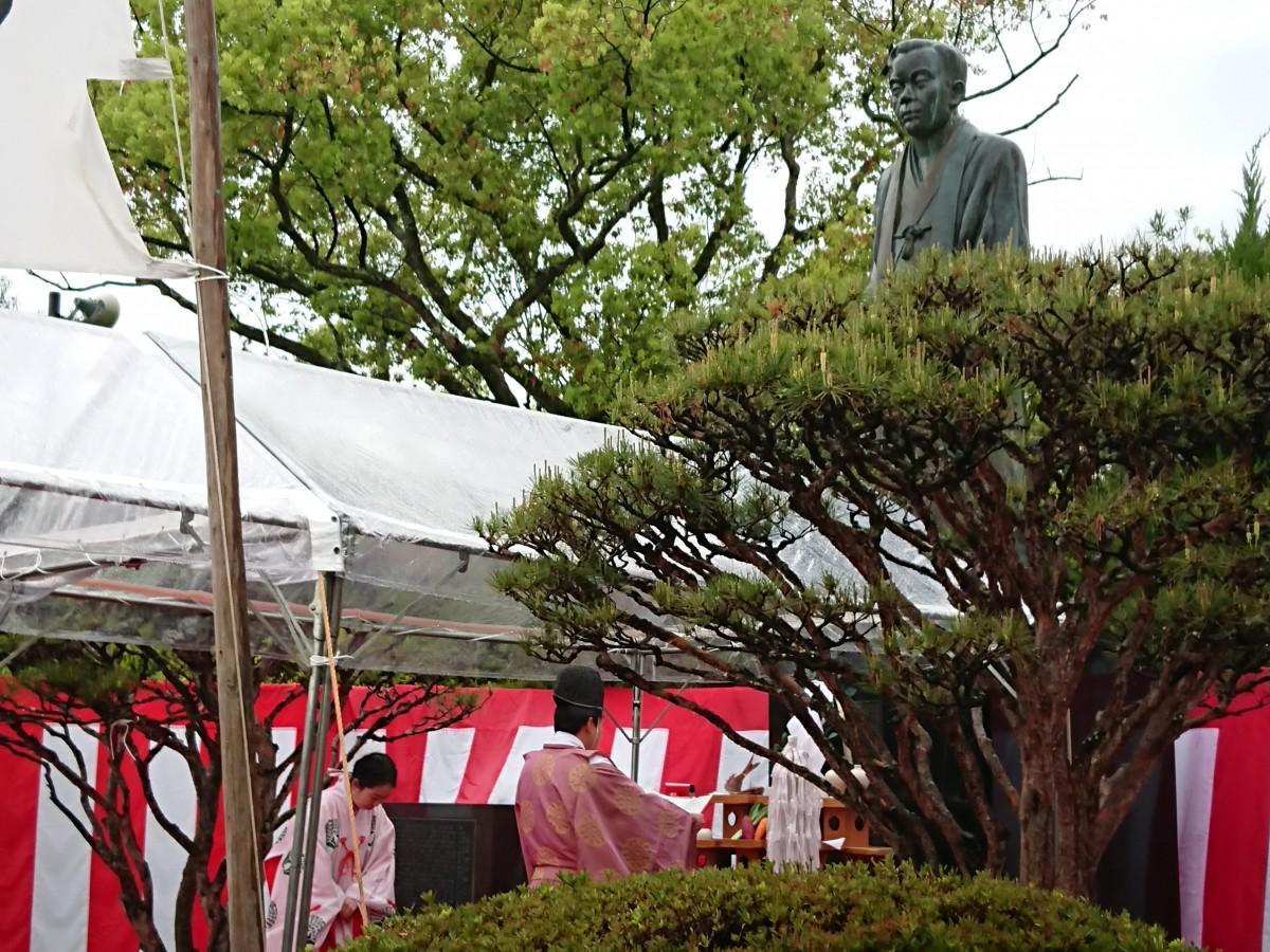 神事の中で、江藤新平の銅像に邪気を払う祝詞をささげる様子