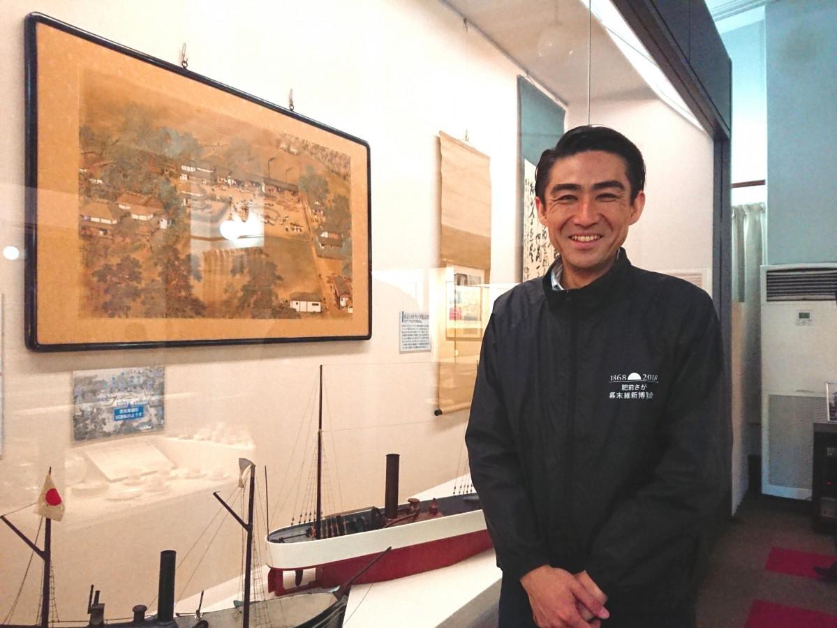鍋島直正が実際に見た蒸気船の雛形など、展示を前に笑顔を見せる富田紘次さん