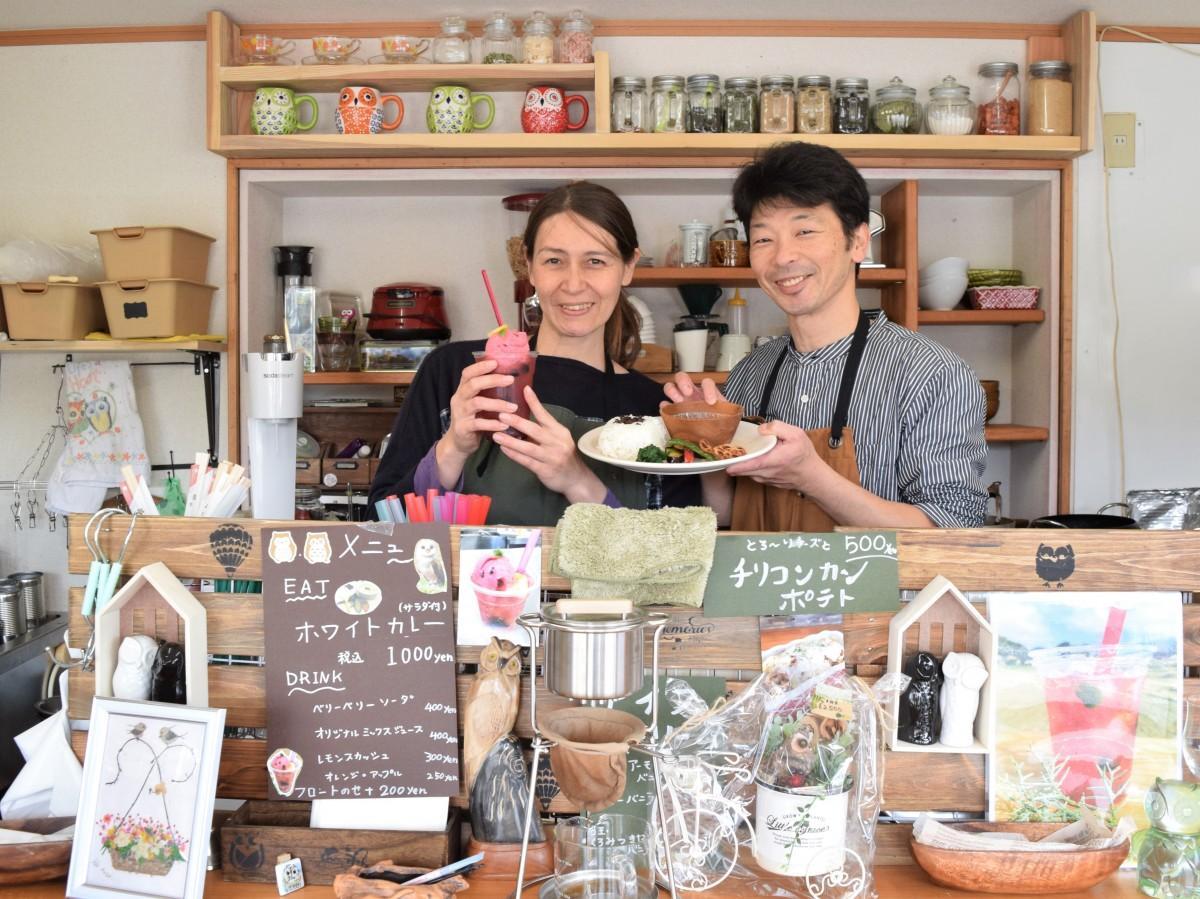 カフェのカウンターで「ホワイトカレー」と「ベリーベリーソーダフロート」をPRする竹原健二さん・アイリーンさん夫妻