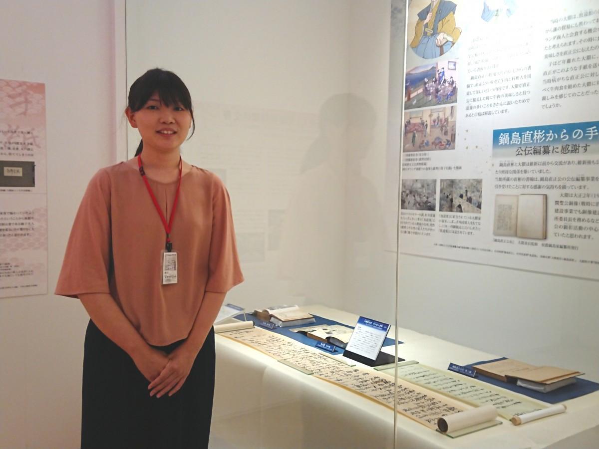 展示とともに写る同館学芸員の大坪由季さん