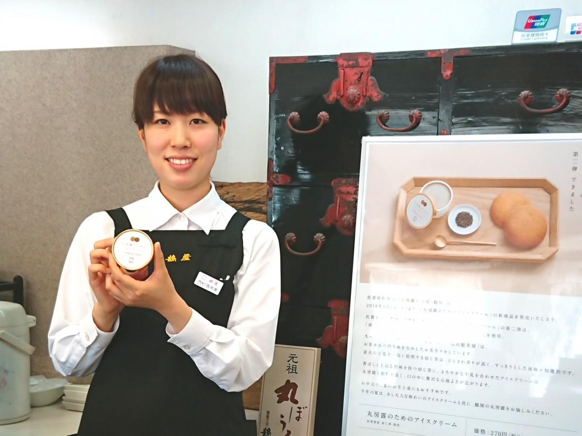 商品ポスターを背に商品をPRする「鶴屋」スタッフの西村香朱美さん