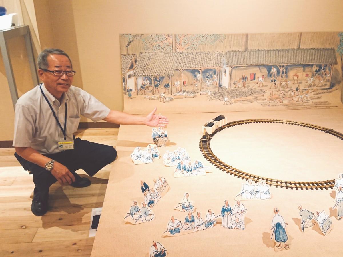 佐賀藩の理化学研究所・精錬方を描いた絵を再現した模型と共に写る佐賀バルーンミュージアムの中野信英さん