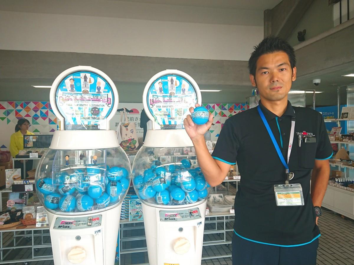 カプセルフィギュアの販売機と共に写る「肥前さが幕末維新博事務局」の井上隆弘さん