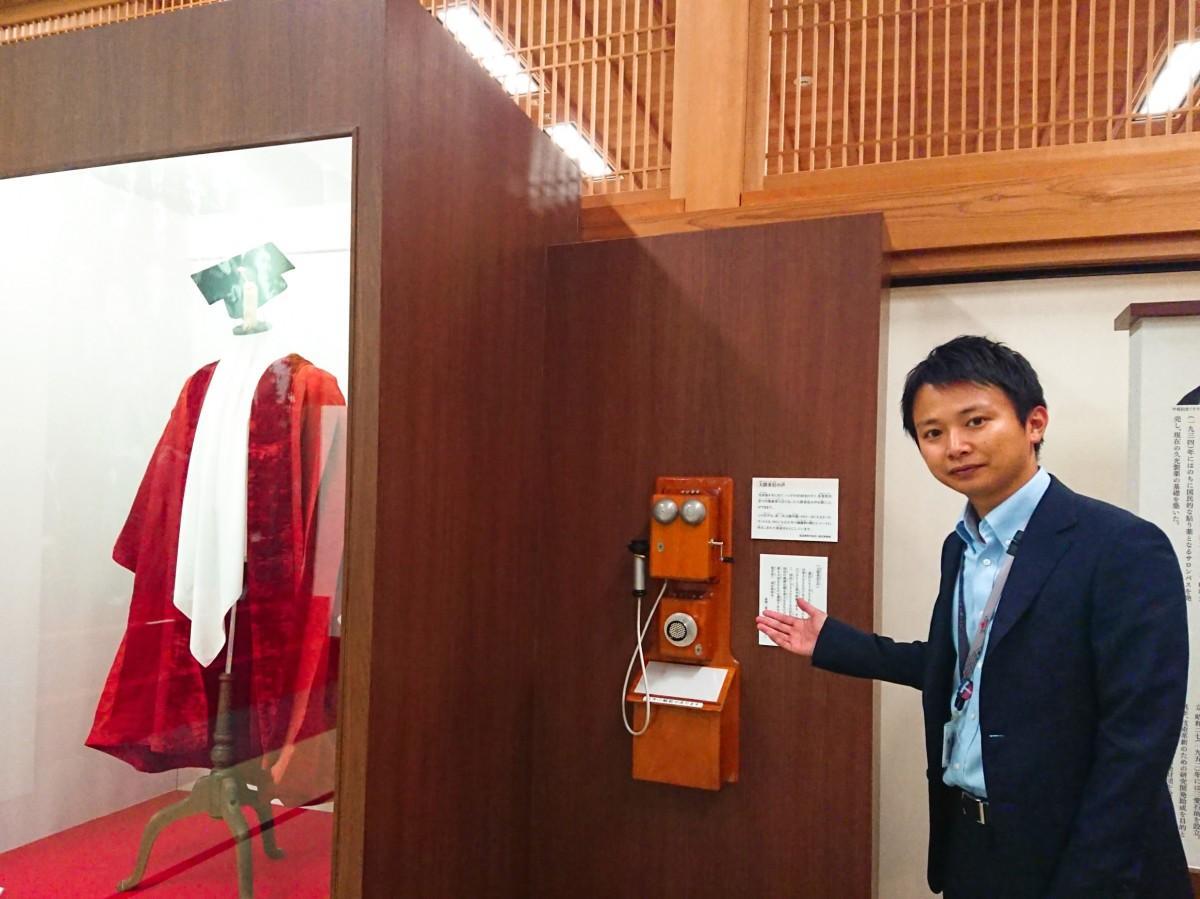 「大隈重信のガウンのレプリカ」らを背に写る、佐賀城本丸歴史館の竹本翔さん