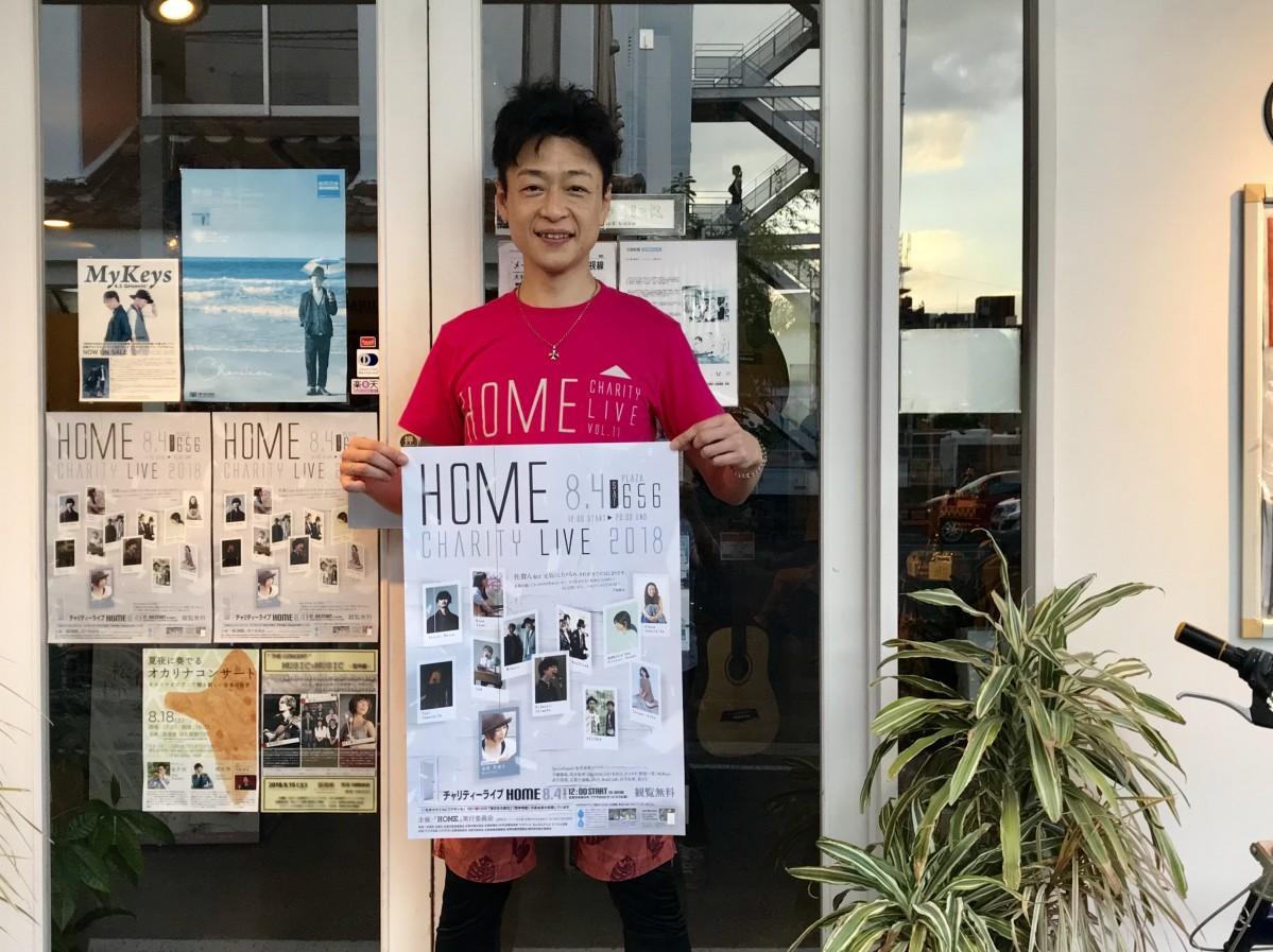 今年の「HOME」オリジナルTシャツを着て来場を呼び掛ける千綿偉功さん