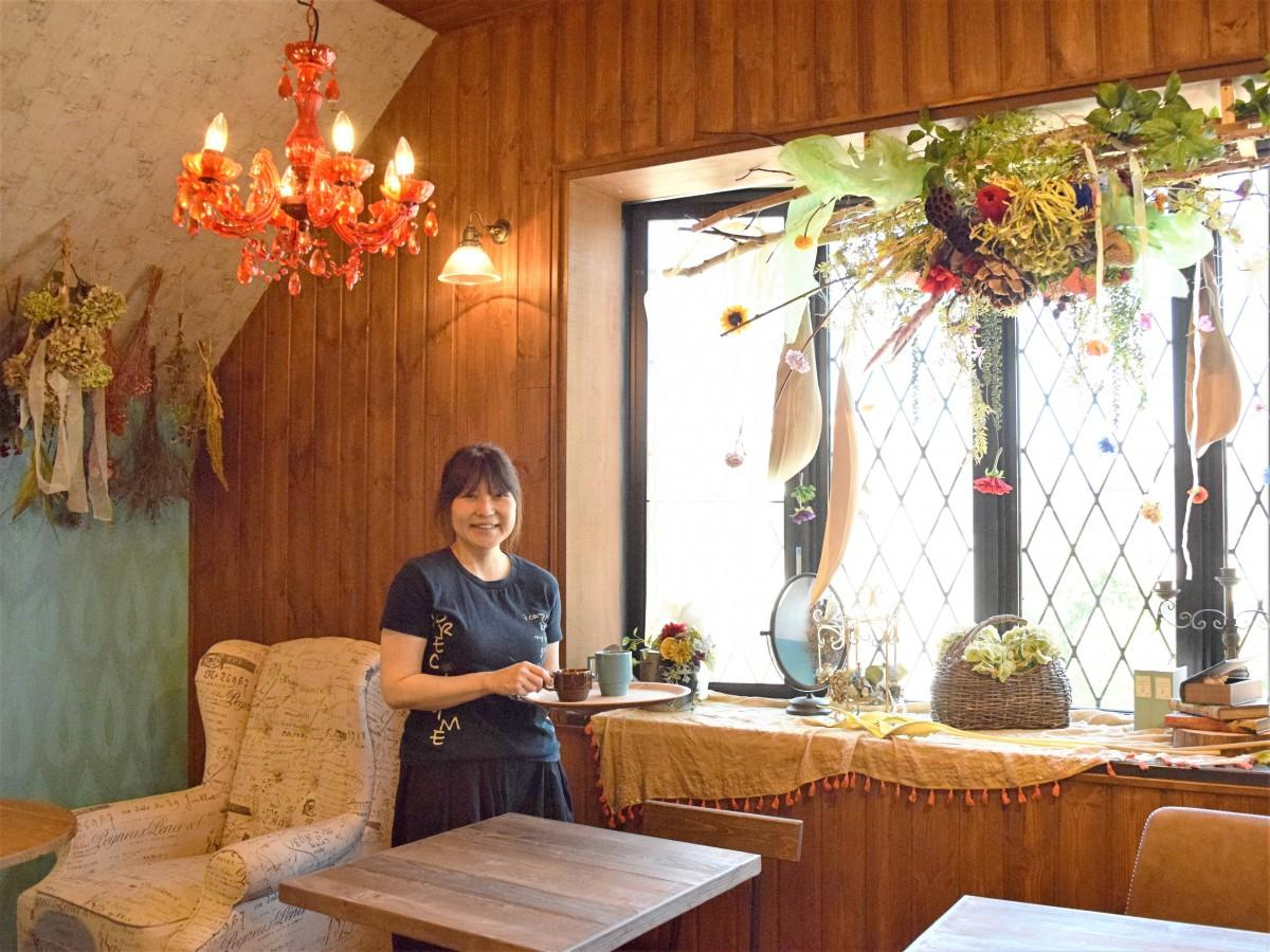 「八子の花カフェ」店内で飲み物を提供する店長の千住麻里子さん