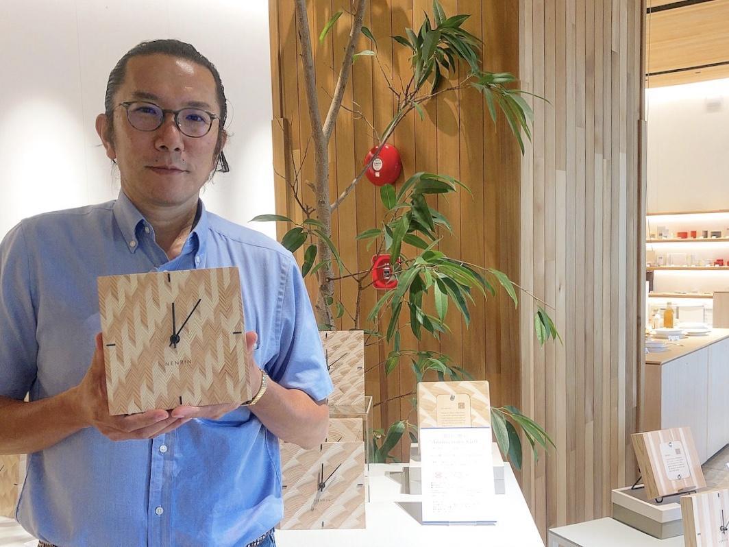 新商品の「NENRIN CLOCK」を手にする専務の実松英樹さん