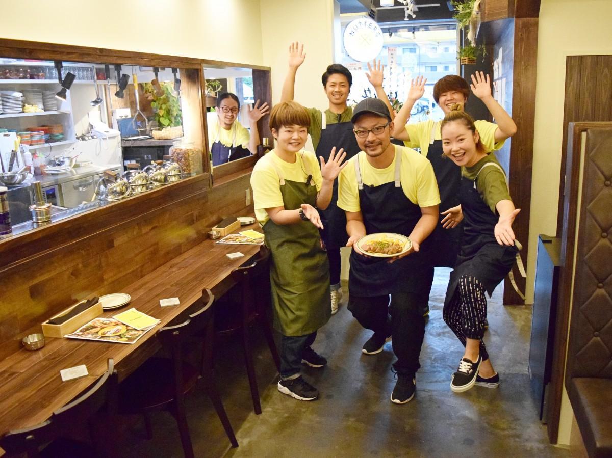 「リブアイステーキ」を手に来店を呼び掛ける店長の山田篤さん(前列中央)と同店スタッフ