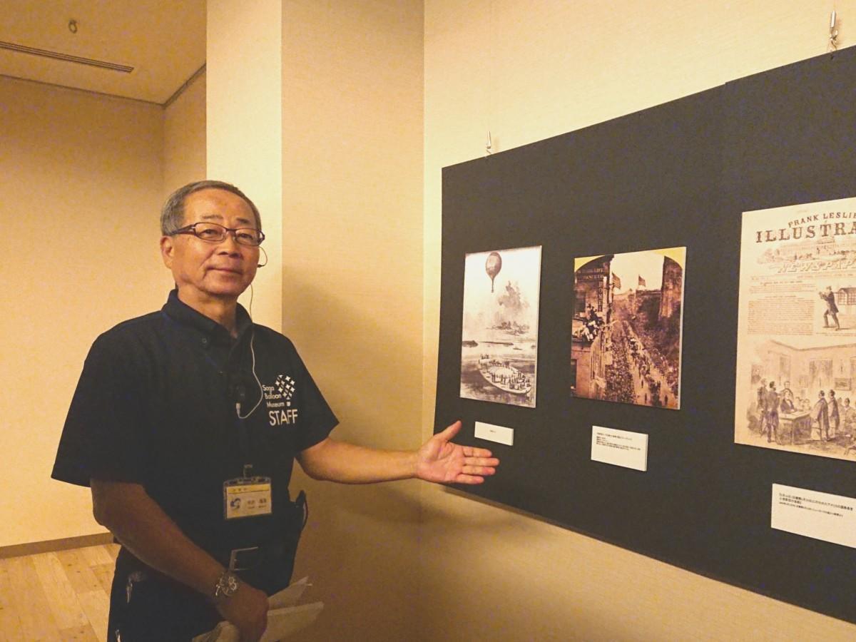 「遣米・遣欧使節団」コーナーの写真の前で来場を呼び掛ける中野信英さん