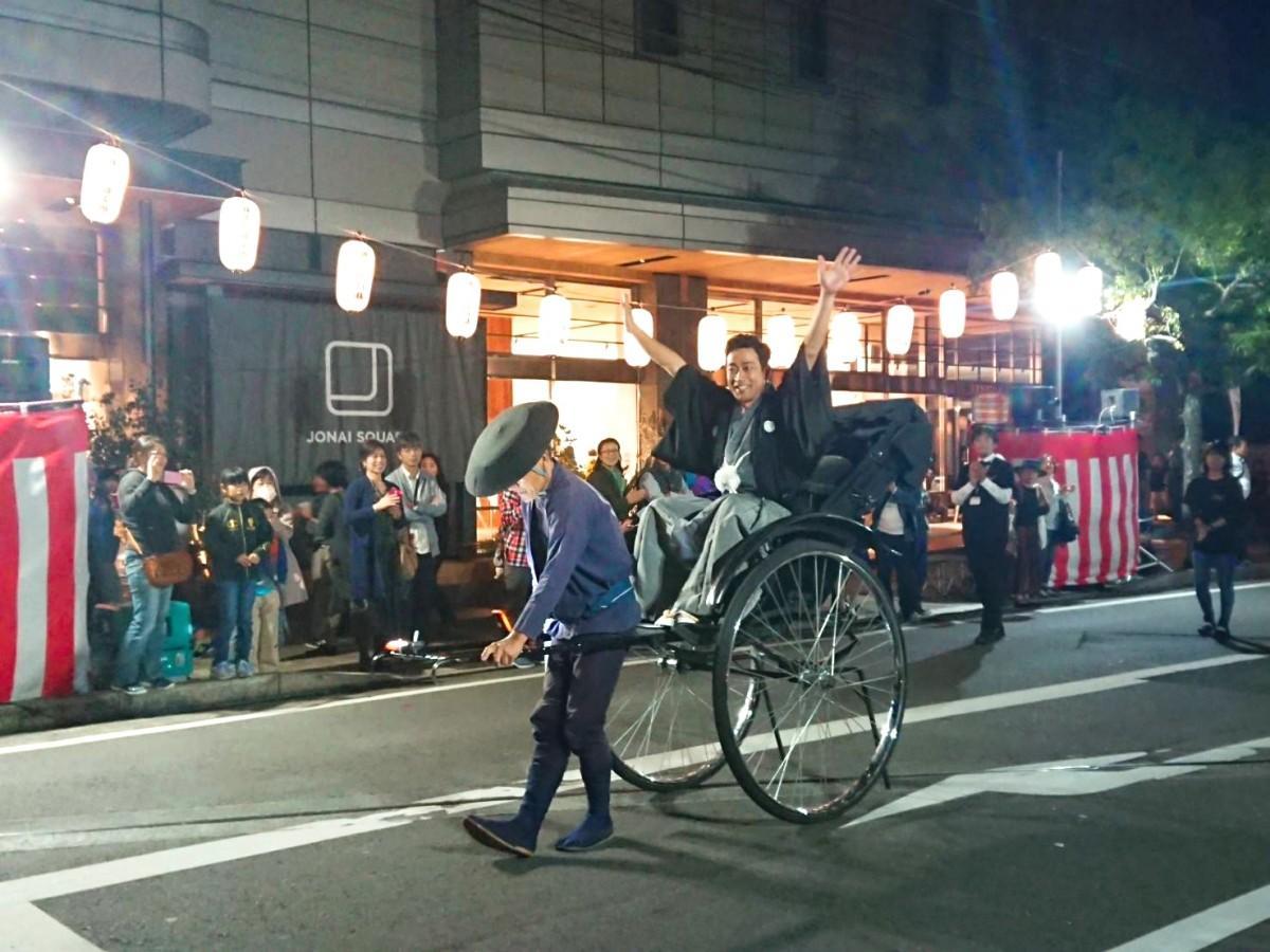 「さが維新行列」で、人力車から両手をあげ笑顔を見せる迫田孝也さん