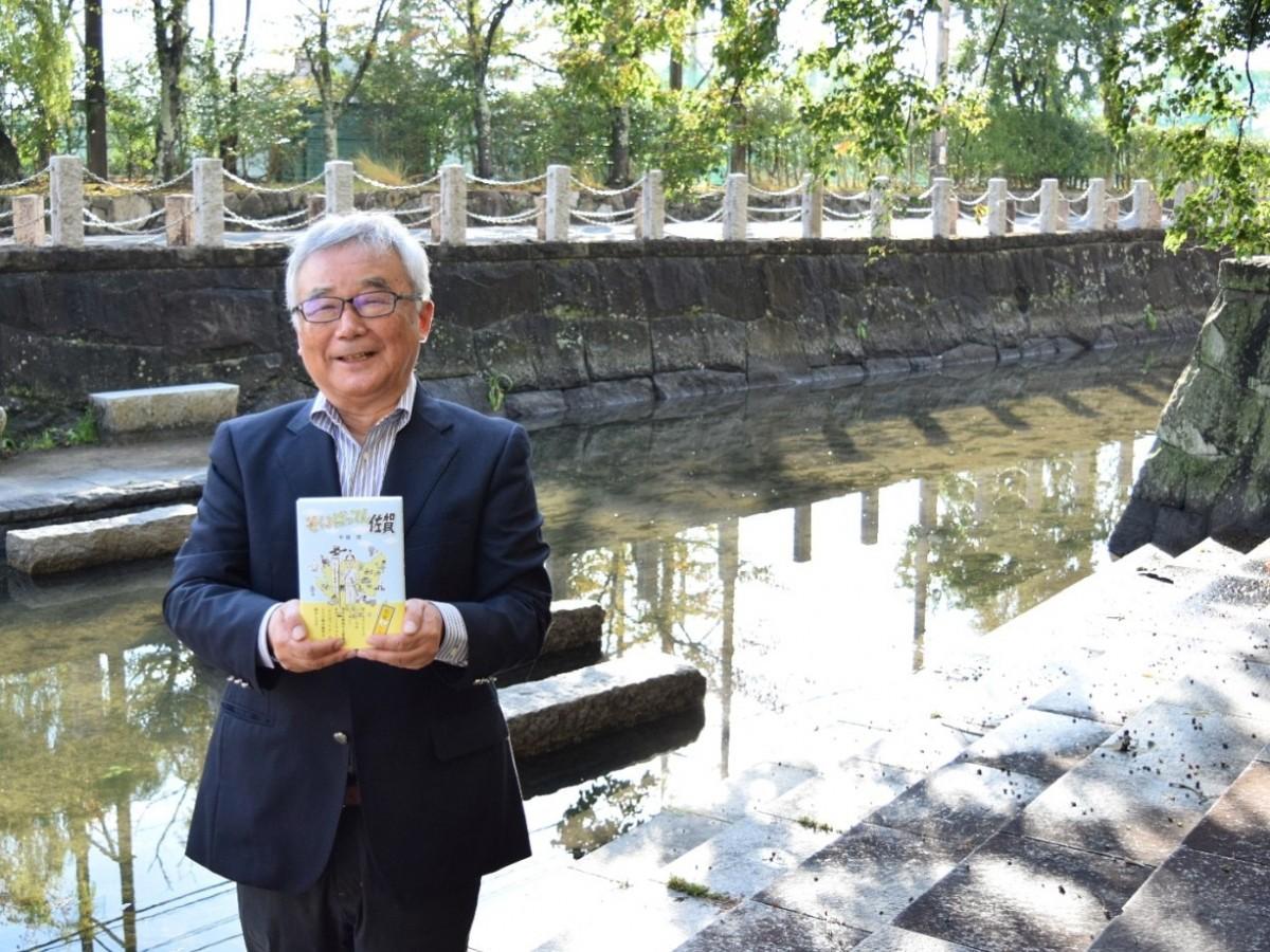 佐賀県庁堀端で自著を手に笑顔を見せる平尾茂さん