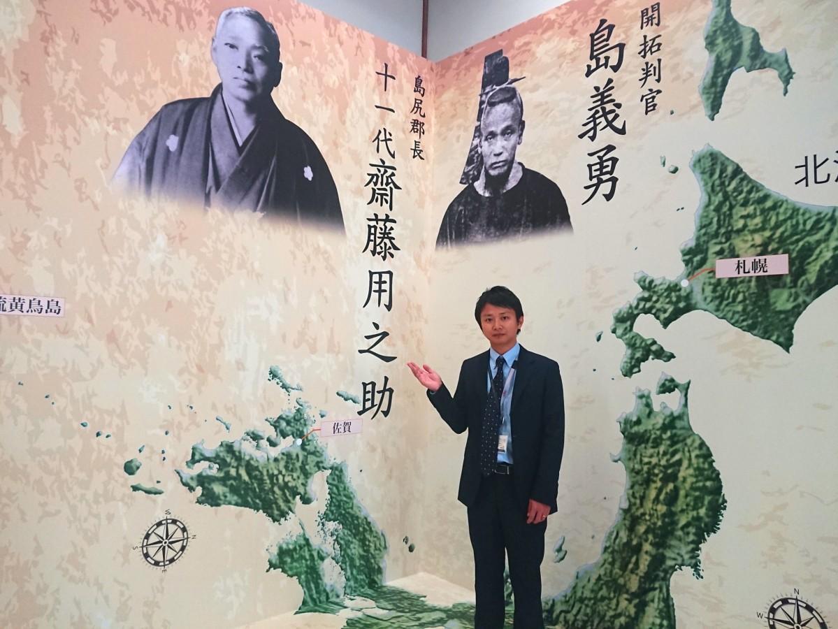 「2人の活躍した地のスケールを感じられる」という高さ3.6メートルのパネルの前で来場を呼び掛ける竹本翔さん