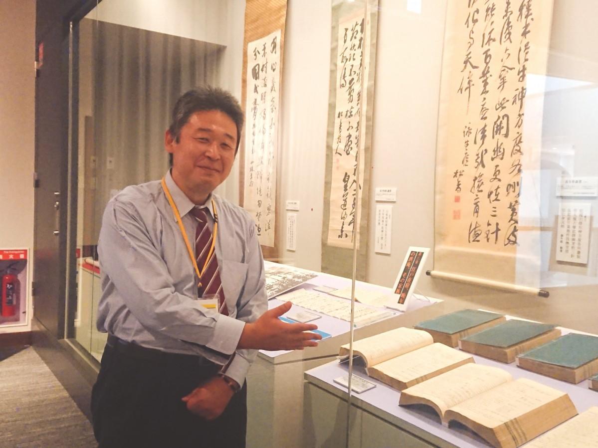 展示された当時のオランダ語辞書「ズーフハルマ」とともに笑顔で来場を呼び掛ける学芸員の近藤晋一郎さん