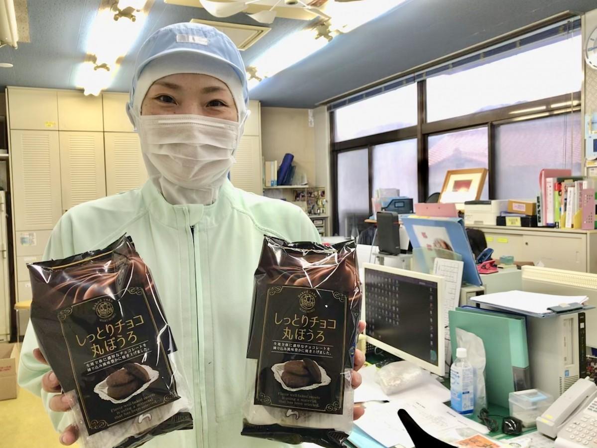 「しっとりチョコ丸ぼうろ」を手にする本村製菓製造スタッフ