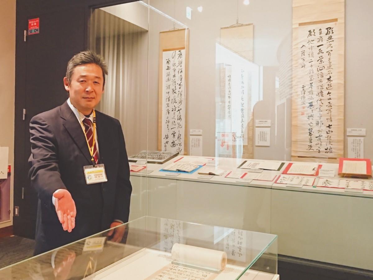 展示品と共に笑顔を見せる学芸員の近藤晋一郎さん