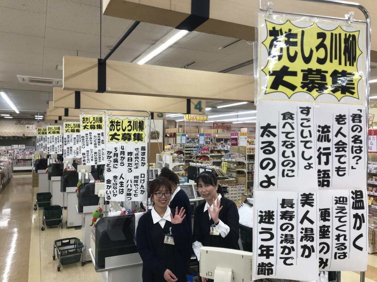 レジ台に掲示する「おもしろ川柳」作品と作品応募をこっそり呼び掛ける店のスタッフ