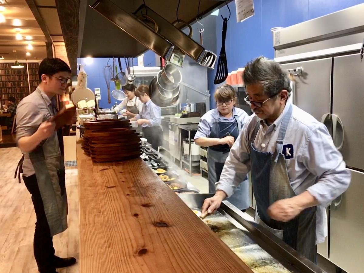 「LOG CABIN」オープン日にあわせてハンバーグメニューを料理する熊本哲郎社長(手前右)