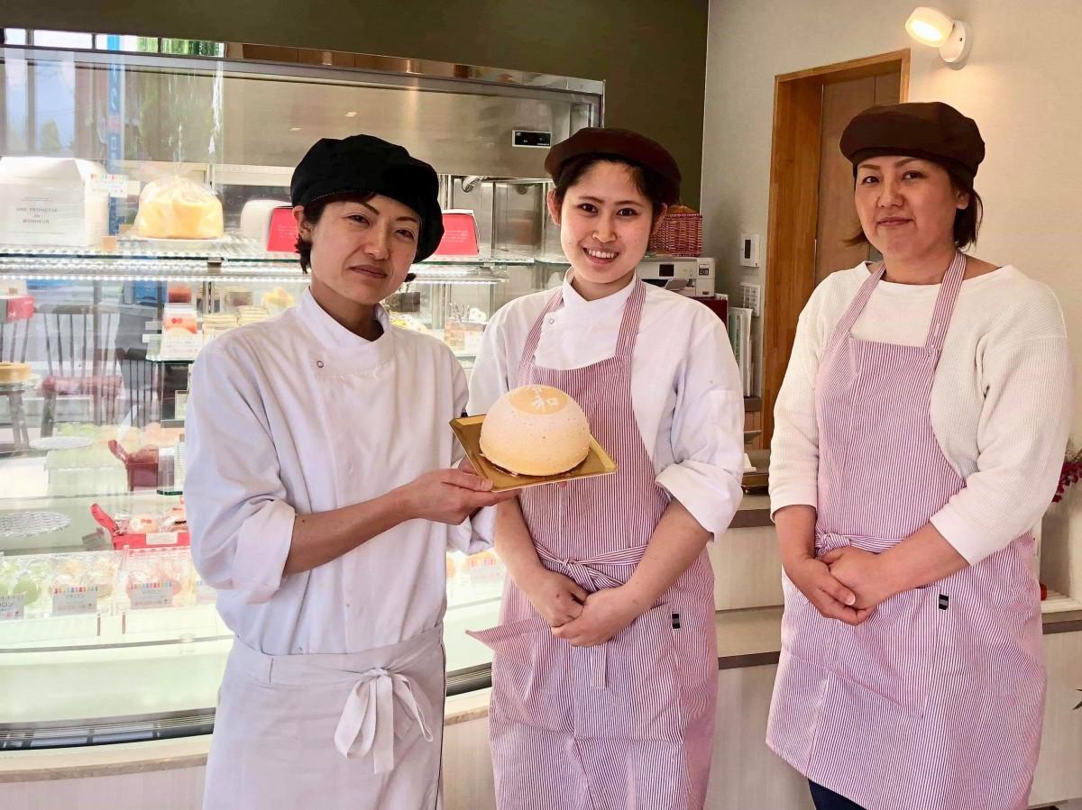 「チーズズコット」を手にする店主の古林茜さん(左)と「akaneiro(アカネイロ)」スタッフ