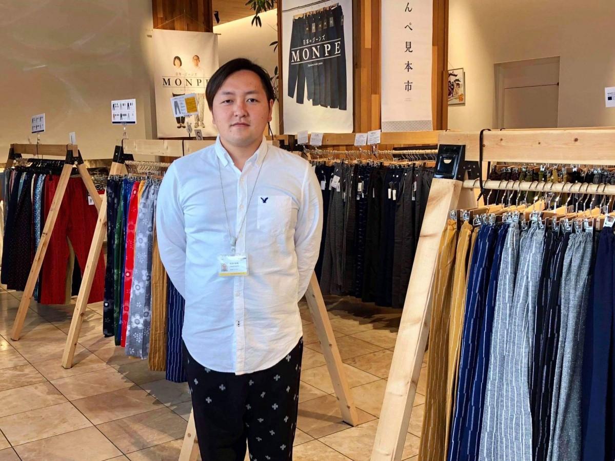 久留米絣のもんぺを着用し、イベントPRする「JONAI SQUARE」の坂田和馬さん