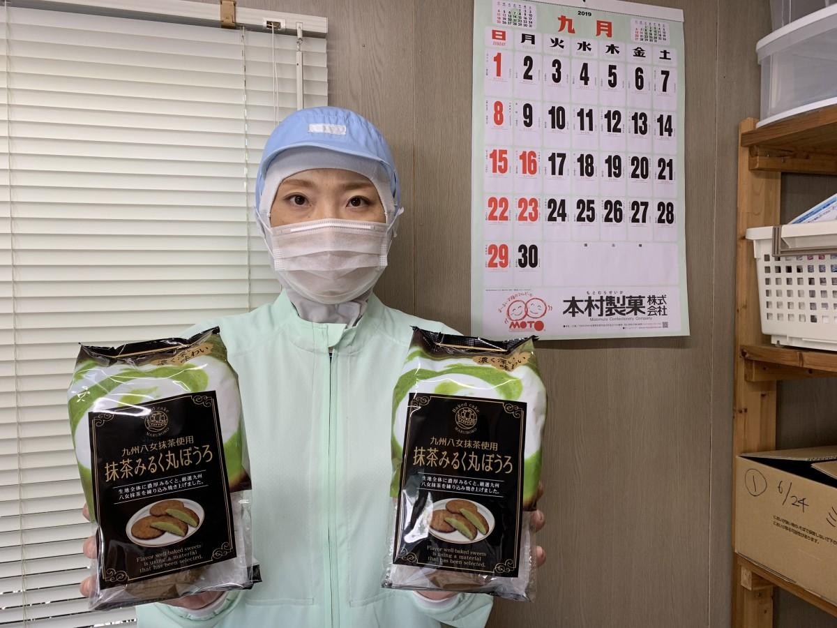 「抹茶みるく丸ぼうろ」を手にする本村製菓製造スタッフ