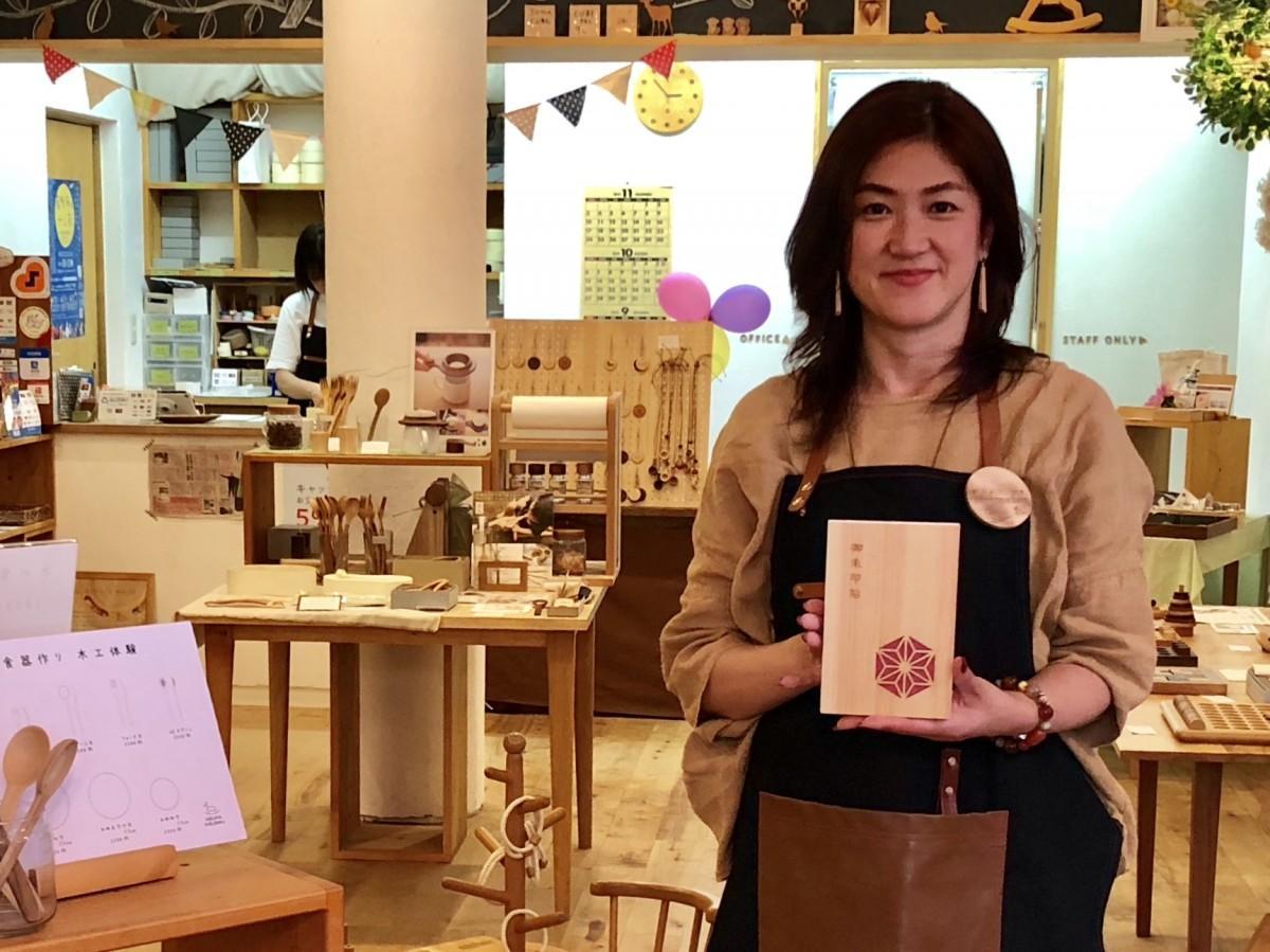 「木の御朱印帳」を手にする店主の廣松美紀さん