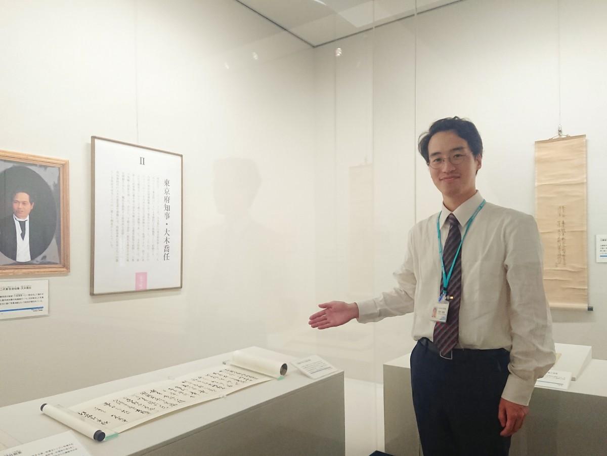 東京府知事としての大木喬任の活躍を示す資料を前に、来場を呼び掛ける学芸員の芳野貴典さん