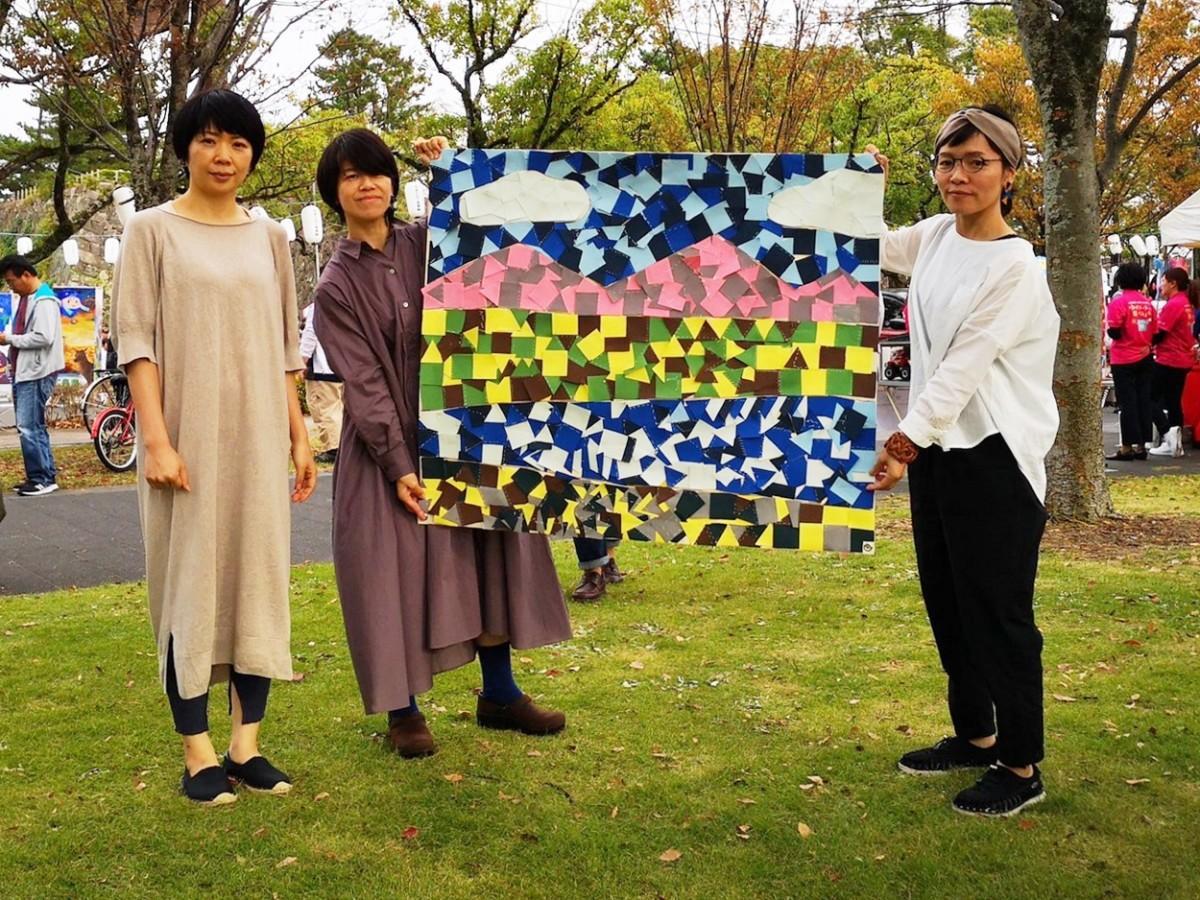 (右から)完成したフラッグを掲げるタカオユミコさん、河原由紀子さん、伊藤友紀さん