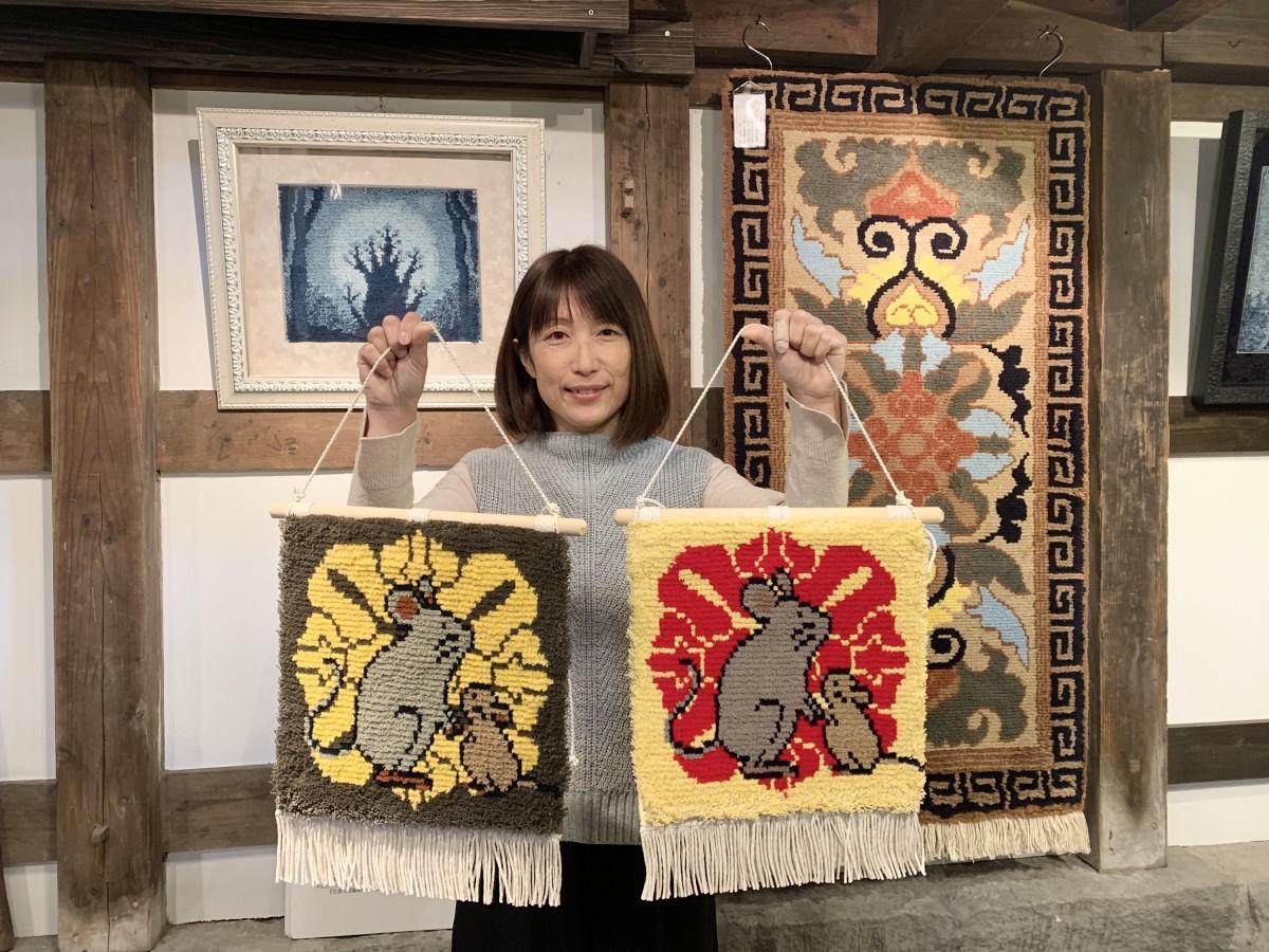 鍋島緞通タペストリー「牡丹に子」を手にする「織ものがたり」デザイナーの木下由紀子さん