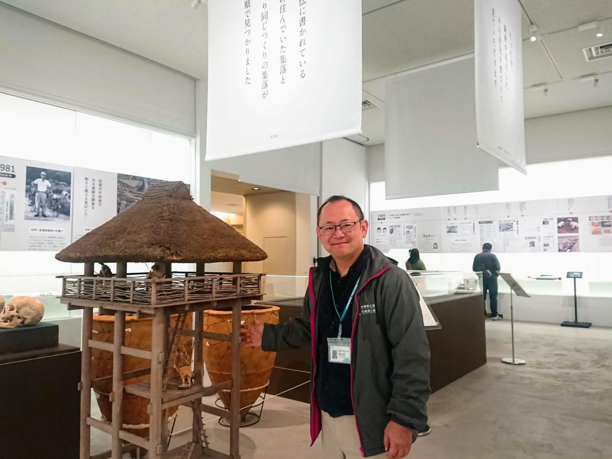 自身が手掛けた展示とともに笑顔を見せる佐賀県立美術館学芸員の細川金也さん